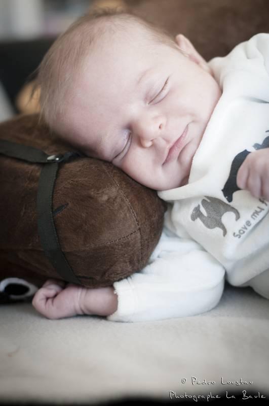 bambin qui dort sur sa peluche avec le sourire-photographe-la-baule-pedro-loustau